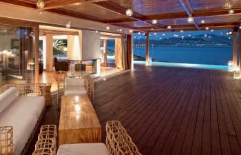 Η ευρύχωρη βεράντα µε το ξύλινο deck επικοινωνεί οπτικά µε την εσωτερική αίθουσα